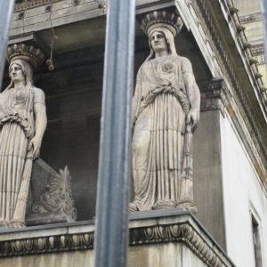 ...and two bouncers, standing like caryatids: those thick-necked women seen holding up porches outside Greek temples and St Pancras Parish Church.